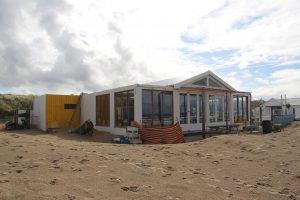 Het strandpaviljoen van buten gezien. De unit met de geel geverfde bekleding is de toiletunit
