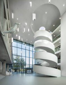 Het hoge lichte atrium is het hart van de school, met links de oudbouw en de receptiebalie  en rechts de nieuwbouw. De spectaculaire stalen wenteltrap heeft onderaan een doorsnede van 8,2 meter en wordt naar boven toe steeds smaller. De trap hangt vrij aan de verdiepingsvloeren van de nieuwbouw.