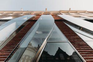 De gevel bestaat uit panelen van gelamineerd, ongehard, ijzerarm glas, met gebogen en rechte lijnen die door silicone naden zijn verbonden met de glazen panelen in rvs-randprofielen.