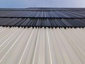De gevels van de sporthal zijn geheel met gevouwen aluminiumplaten bekleed, de witte plint in een sterkere variant dan de zwarte erboven