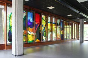 Begane grond van de oudbouw. Links:  de theaterzaal met een gerestaureerde glas-appliqué van kunstenaar Joop van den Broek uit 1972