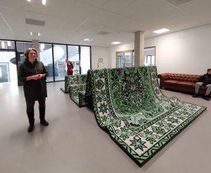 Voor elk cluster ontwierp PRO een uniek meubel. Architect Dorte Kristensen bij zitmeubel 'Geland tapijt', dat bestaat uit een op maat gemaakt tapijt,  aangebracht op multiplex gegolfde onderbouw