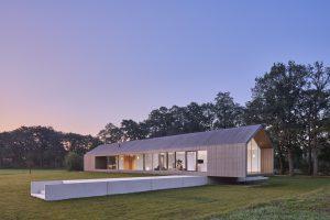 De schuurwoning heeft een langgerekt volume van één bouwlaag met een kap, waarin het woonhuis, een carport en bijgebouw zijn ondergebracht