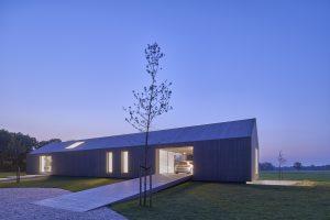 De hoofdentree van het woonhuis bevindt zich in de carport en is bereikbaar via de houten oprit.