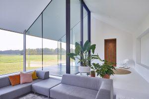 Het woonhuis heeft een open plattegrond met witte vloeren, wanden en plafonds. De woonkamer aan de noordzijde heeft een verdiepte zithoek met en een glazen patio