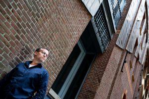 Dennis Reek van Ridder Skins for Buildings bij een kunstwerk in RVS van Jano van Gool op de gevel van Pakhuis Wilhelmina aan de Veemkade in Amsterdam (Foto Martin Wengelaar)