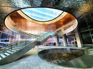 """Shopping Mall Turnova, Turnhout (B), B-architecten 2019-20. Nieuwste ontwikkeling in metalen bekleding zijn de 3D formed skins in spiegel rvs, hier toegepast in de plafonds. """"Net kabbelend water…"""""""