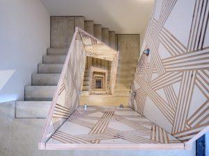 Voor de binnentrap bedacht het Eindhovense ontwerperscollectief Envisions een streeppatroon over de alle vier verdiepingen langs de dichte leuning in betonplex omhoog loopt, een visuele referentie naar de gestreepte buitengevel