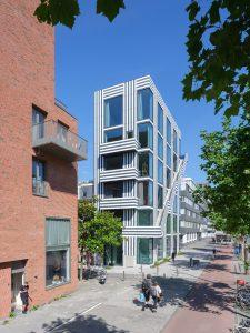 Op de hoeken van het gebouw bieden glazen vensters van vloer tot plafond zicht over de Wibautstraat