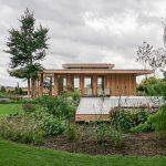 Houten buitenhuis verweven met groene omgeving