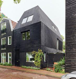 De gevel en het hellende dak van de woning zijn bekleed met zwart gebrand hout. Een verwijzing naar de waterlandstijl