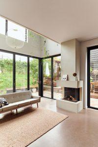 De pui is geheel te openen. De vloer loopt door van woonkamer naar tuin. De haard is afgewerkt met betonstuc